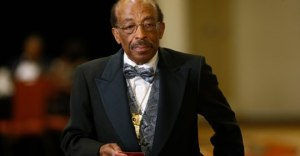 Image: photo of Black man, balding with a mustache and wire-framed glasses, wearing a suit, a flowered bow tie, and a matching vest.