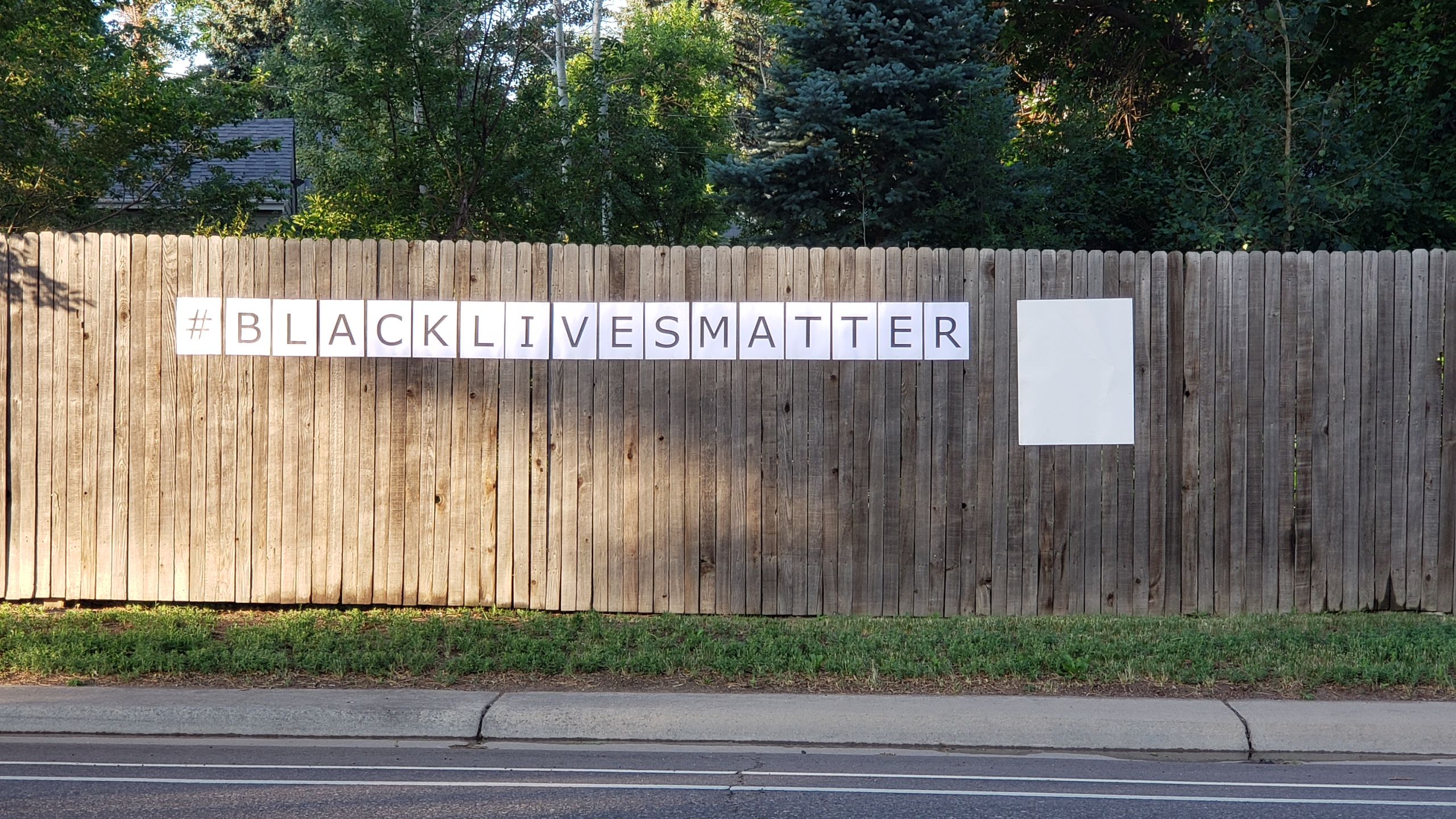 "Wooden fence with ""#BLACKLIVESMATTER"" and a blank poster board stapled to it, photographed from across a residential street."