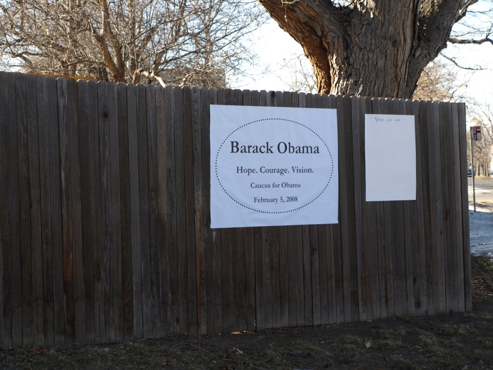 "Wooden fence with poster reading ""Barack Obama. Hope. Courage. Vision. Caucus for Obama. February 5, 2008"""