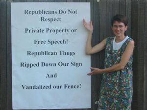 "Me (white lady, brown hair, flowered sundress) standing by a sign that reads, ""Republicans do not respect private property or free speech! Republican thugs ripped down our sign and vandalized our fence."""