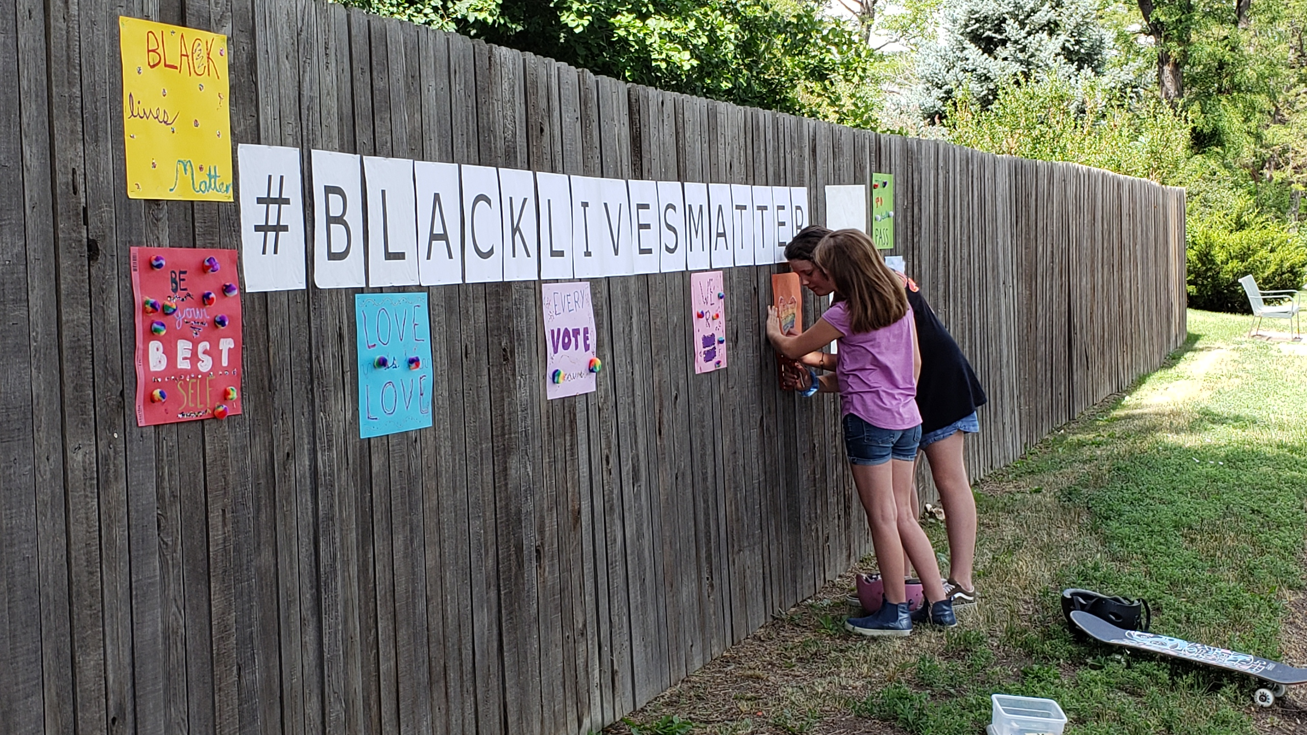 Olive (white girl; purple shirt; denim shorts) and Janie (white girl; black tshirt; denim shorts) working together to staple a sign under the #BlackLivesMatter sign. Two helmets and a skateboard are on the ground near their feet.