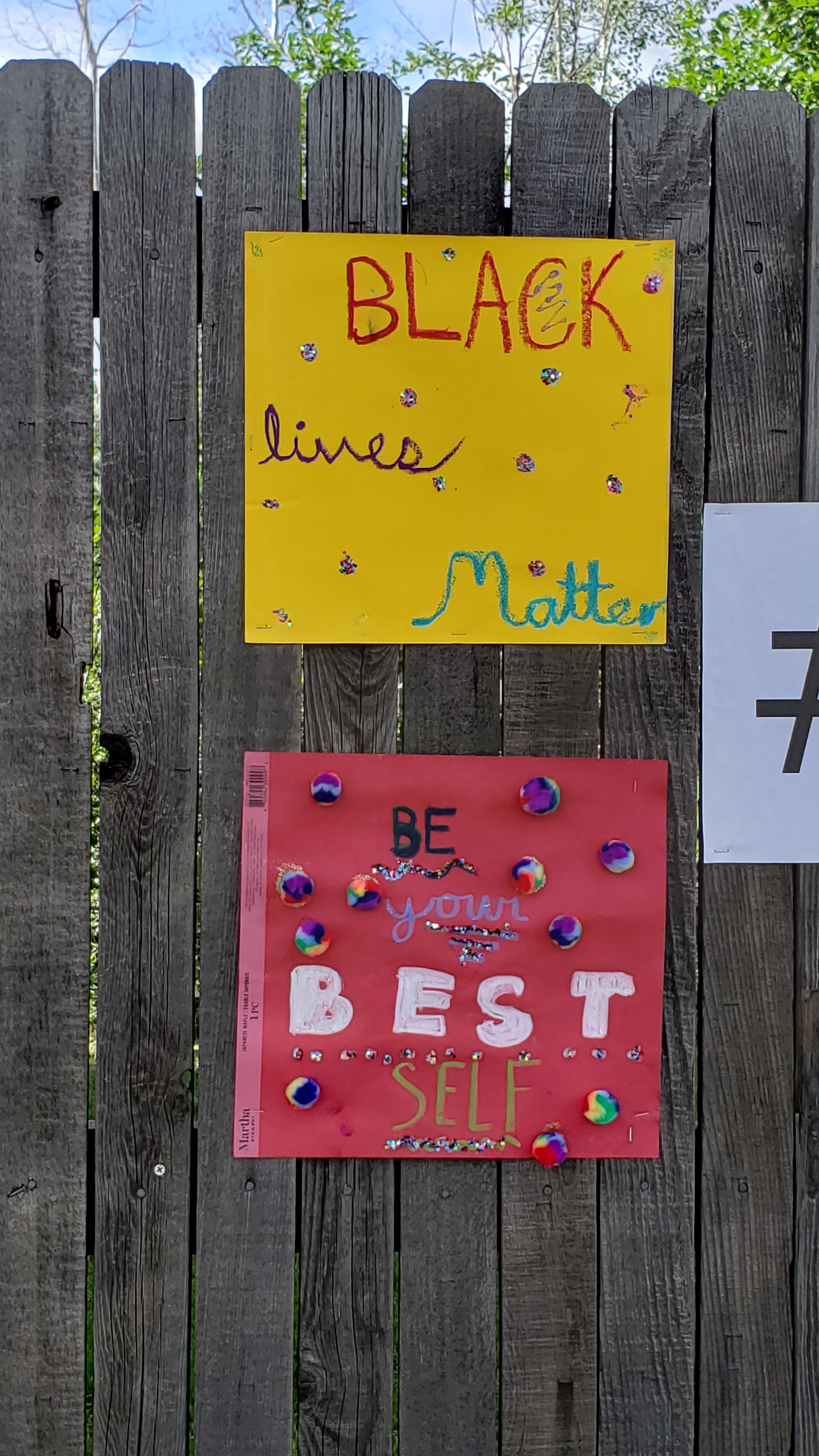 "Two construction paper signs. The top yellow paper with the words ""Black lives Matter"" in various colored inks with glitter. The bottom with the words ""Be Your Best Self"" with multicolored cotton balls."