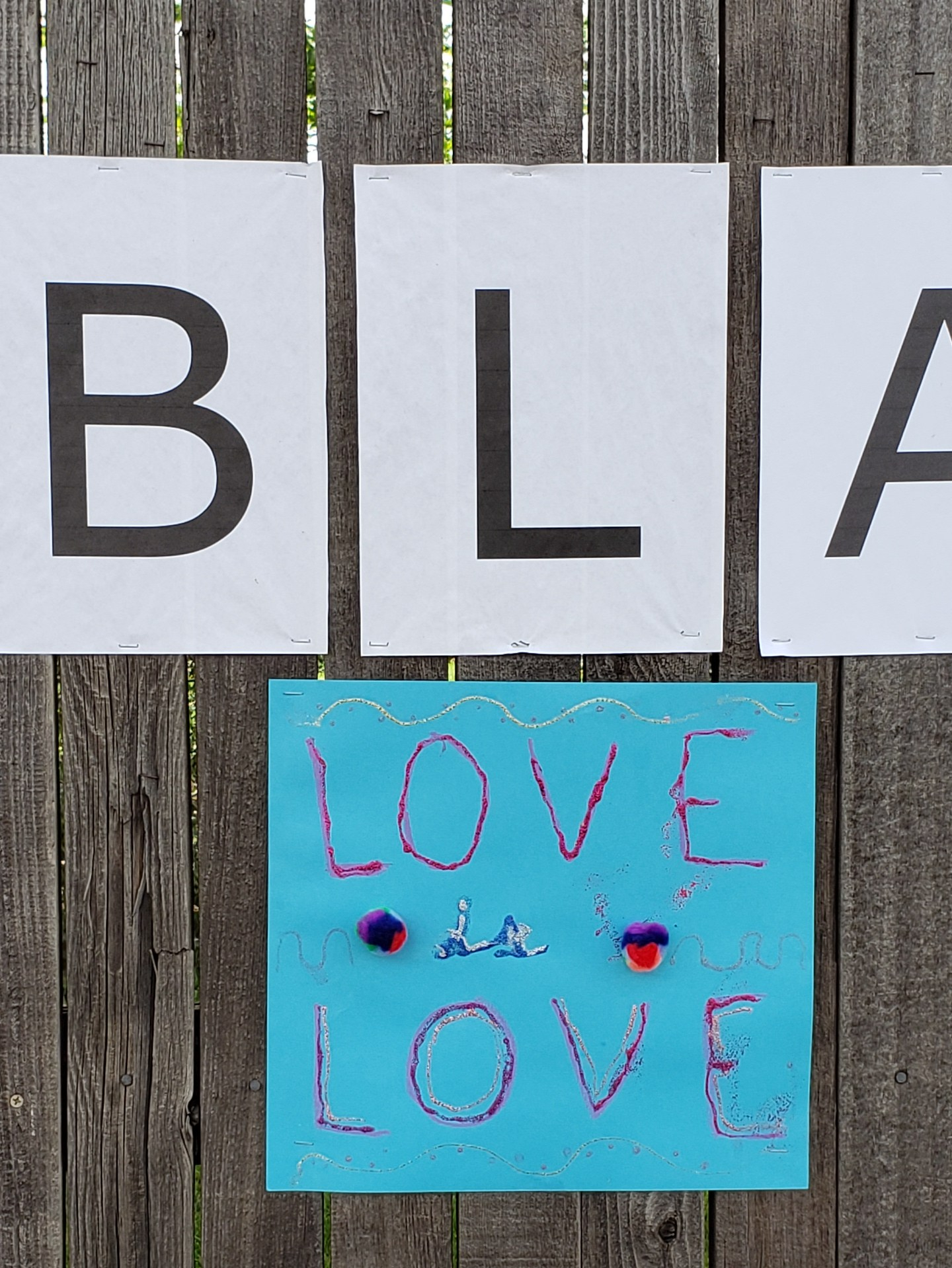 "Blue construction paper sign that reads, ""Love is Love"" in red and blue ink with glitter and two multicolored cotton balls."
