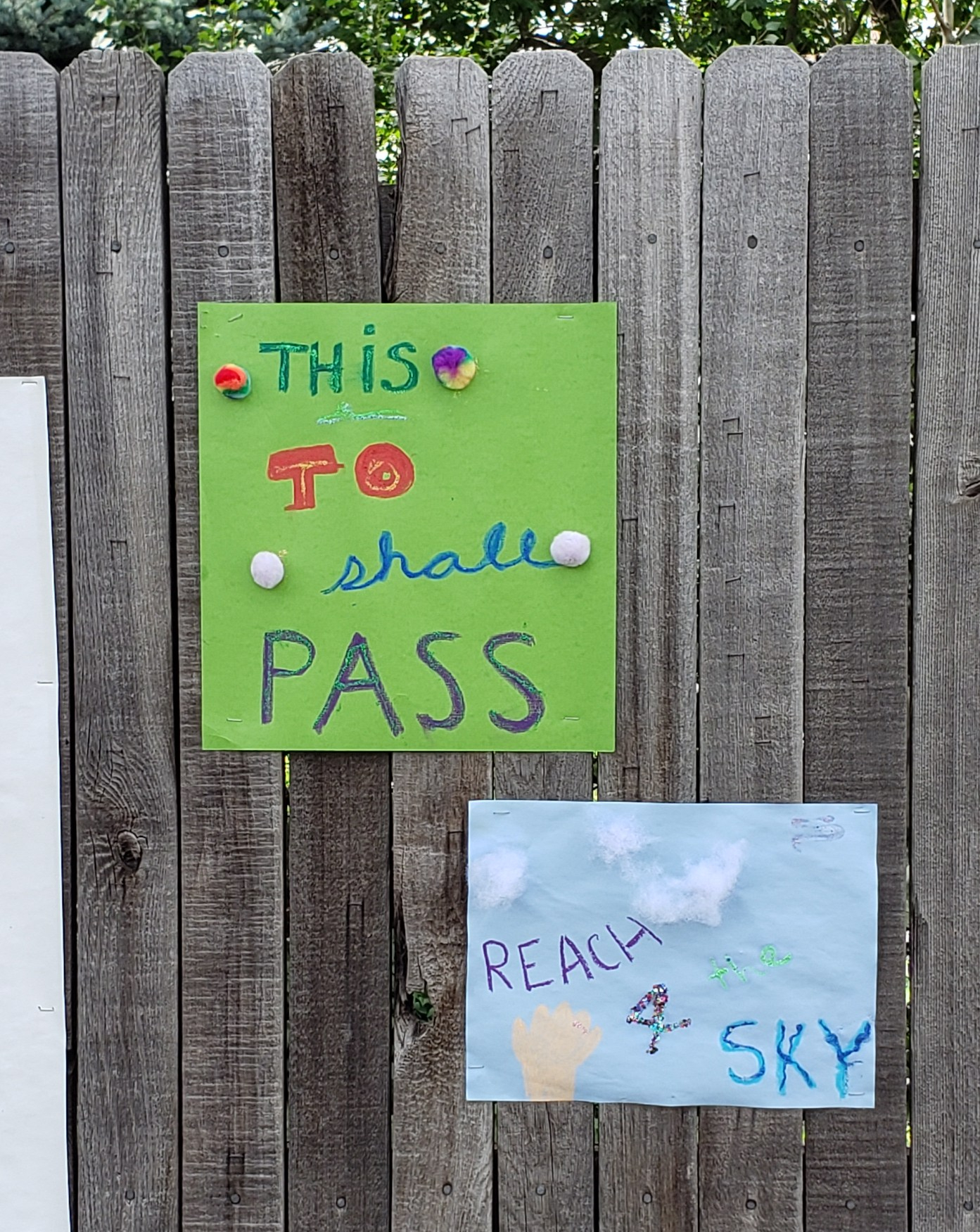 "Two construction paper signs. One green that reads ""This to shall pass,"" in various colors of ink with rainbow cotton balls dotted around. The second is on light blue paper and says Reach 4 the Sky with cotton ball clouds and a light-colored hand reaching up from below."