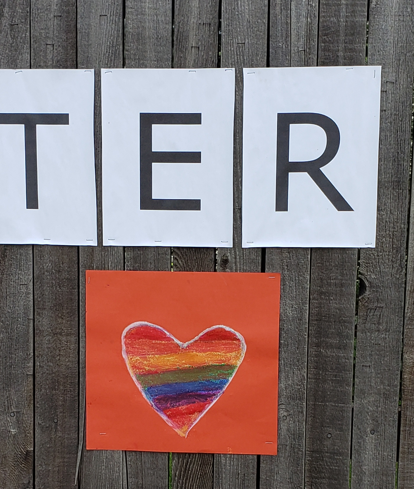 Orange construction paper sign with a heart outlined in white and filled in with rainbow colors.
